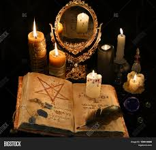 halloween text symbols mystic still life with black magic book and mirror in candle light