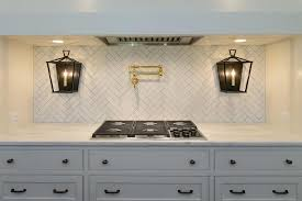 herringbone kitchen backsplash white herringbone backsplash tiles with iron and glass lanterns