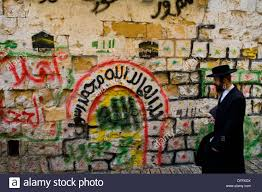 Wall Scenes by An Orthodox Jewish Man Walks By A Colorful Wall Covered With Arab