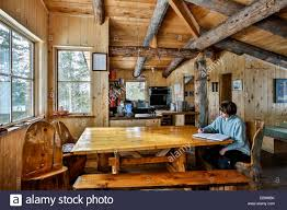 woman writing in guest log on dining room table kitchen in stock