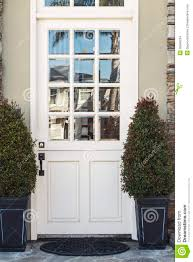 front door modern white front door to modern home flanked by plants stock photo