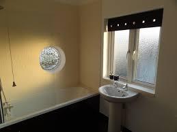 limestone mosaic tiles on windowsill and enclosing bath shower