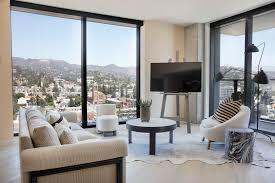 inside the new hollywood proper hotel where monthly rents start the living room of a furnished two bedroom unit the soundproof windows extend from the floor to the top of the nine foot ceilings