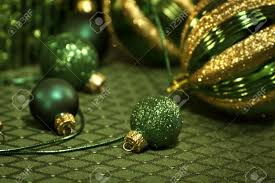 closeup of green and gold ornaments on tablecloth stock