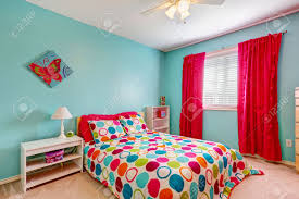 cheerful bedroom interior in turquoise color with bright red