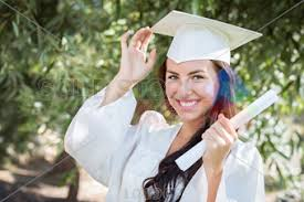 white cap and gown stock photo of haired smiling graduate wearing white cap