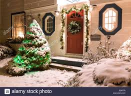 the front door of a snow covered family home decorated for