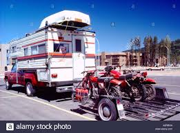 motocross dirt bikes rv pickup camper truck carrying rowboat on roof and pulling