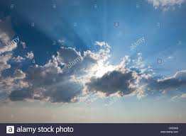 clouds and sun with sun rays in the sky stock photo royalty free