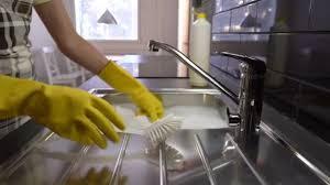 cuisine mouvement la ménagère lave la vaisselle dans l évier dans la cuisine