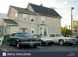1966 dodge charger mg and classic cadillac in front of house in