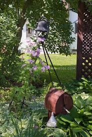 shade garden with birdhouse clematis vine in pink flowers