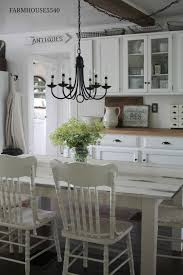 two matching candle chandeliers over farmhouse table in front of kitchens