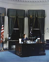 president john f kennedy poses for portrait at oval office desk