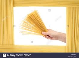 man holds raw pasta capellini the frame is made of the same
