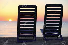 Plastic Beach Chairs Two Plastic Chairs Stand On Beach Near Water With View On Sunset