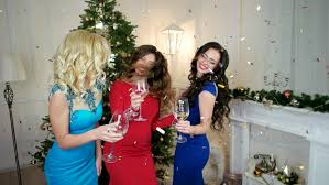 cheerful of friends near the decorated tree drink