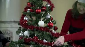 pregnant woman decorating christmas tree with baby booties stock