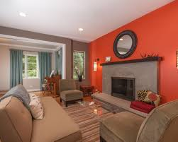 orange accent wall with grey colored fireplace for cozy living