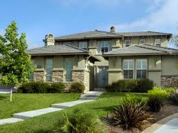 green prairie style home stone accents wide horizontal rooflines