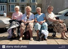 four elderly women on a day trip to the seaside sitting on a