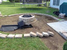laying the rumble stone border for fire pit backyard patio