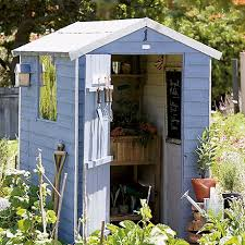 a pale blue and ivory shed situated in the centre of a packed