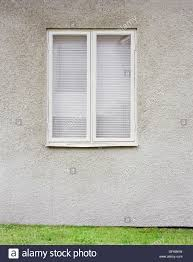 exterior of double window with white venetian blinds on gray wall