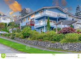 large three story tall blue house with summer landscape and rock