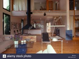 glass table and wooden flooring in open plan double height modern