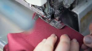 dressmaker working on sewing machine in studio at table