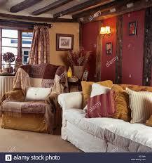 cottage livingroom patterned throws on armchair in nineties cottage living room