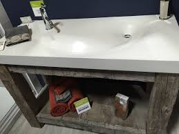 polished concrete bathroom sink with reclaimed wood vanity brick