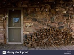 vintage stone cabin porch with stacked firewood outside on the