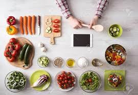 légumes à cuisiner homme de cuisiner à la maison avec la tablette à écran tactile des