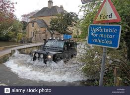 a land rover defender exiting a flooded ford on the river windrush