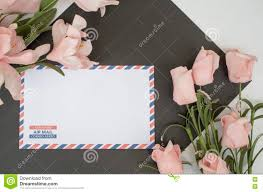 mail flowers flat lay composition with air mail envelope and flowers stock