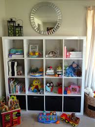 furniture white ikea toy storage filled with books and doll and