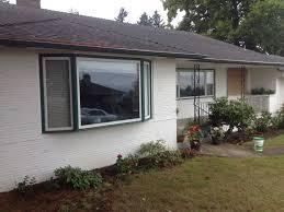 exterior cedar shakes above house garage door white wooden coplay