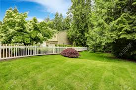 beautiful front yard landscape with white fence red bush on