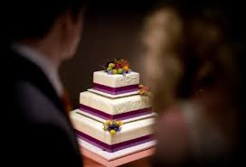 white wedding cake purple ribbon small floral details in yellow