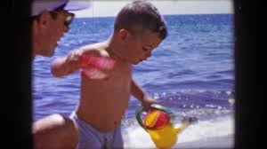 1955 boy exiting busy beach coming to play with dad on water