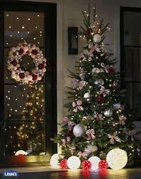 christmas tree with white lights and red bows sweeten up your christmas tree with candy cane inspired ribbons and