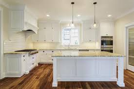 luxury white kitchen with island and hardwood flooring kitchen