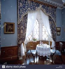 gothic pelmet above patterned blue drapes in blue diningroom at st