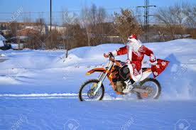 snow motocross bike santa claus riding on a motocross bike in a red coat through