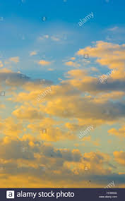 yellow clouds with sun rays in the blue summer sky stock photo