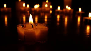 small flower shape candles burning at on a wooden table
