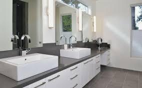 dark countertop white bathroom cabinets under framed round mirror