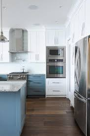 white upper cabinets with blue lower cabinets with pale blue glass